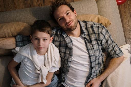 Сидят двое, отец и сын. Мужчина слегка обнимает ребенка, а он доверительно положил голову ему на плечо: лучший друг – это папа.