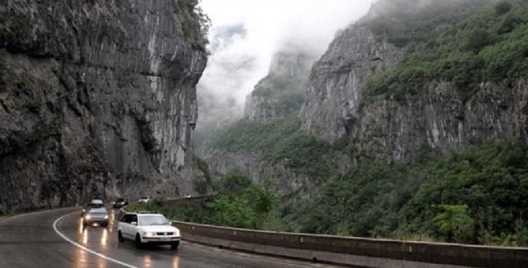 Машины с включенными фарами движутся по горной дороге. Вечер, туман. Все придерживаются безопасного расстояния на влажной дороге. В горах все зависит от взаимоотношений между людьми.