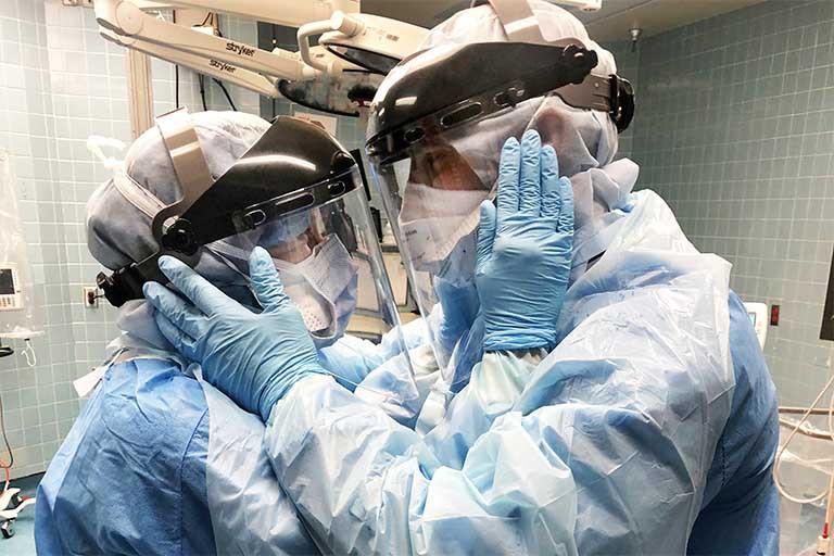 Проблема ответственности перед обществом На картинке два медицинских работника, одетые в защитные костюмы, маски, перчатки, смотрят друг на друга.