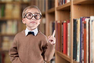 мальчик младшего школьного возраста в очках в библиотеке с осмысленным взглядом, умный, одаренный