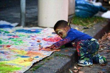 Маленький чернокожий мальчик расписывает лежащую на асфальте бумагу, создает свой художественный образ.