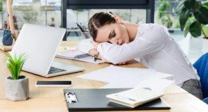 В пустом офисе сидит женщина, устало склонив голову на стопку бумаг. Решить все жизненно важные проблемы невозможно.