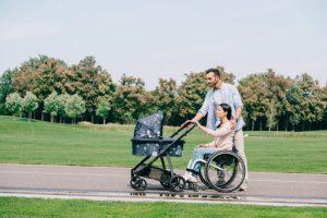 На прогулке молодая женщина в инвалидной коляске катит коляску с ребенком при поддержке мужa: помощь партнера в решении жизненных трудностей – залог семейной гармонии.