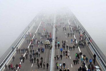 Взаимопонимание между людьми. Большой пешеходный мост, по которому идут группы людей в разных направлениях.