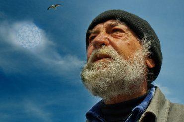 на картинке изображен пожилой человек, дед, который смотрит ввысь на облако, в котором высвечивается невидимая связь всего живого на земле.