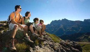 Родители с двумя детьми отдыхают после подъема в горы и, улыбаясь, смотрят вдаль: красота в гармонии с природой.