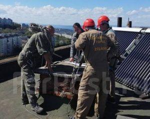На крыше высотного здания команда в костюмах ,оснащенная необходимыми инструментами, го главе с начальником обсуждает план работ