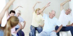 В светлой комнате в доме престарелых проводится гимнастика. Повсюду улыбающиеся лица.