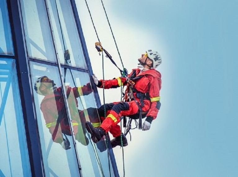Высотник в красном комбинезоне , опоясанный толстым канатом, взбирается по стеклянной поверхности небоскреба.