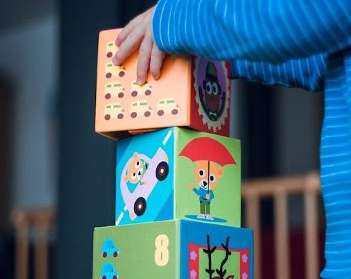 Ребенок увлеченно складывает большие цветные кубики. Улучшение речи у детей связано с развитием моторики.