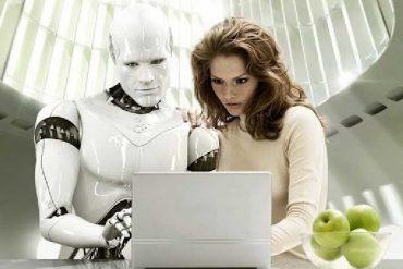 Информационное общество. На первом плане прозрачная ваза с зелеными яблоками. Они смотрят на монитор - мужественный киборг, уверенная шатенка