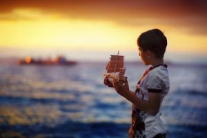 Морской закат. Мальчик держит в руках самодельный парусник. Раздумывая, смотрит вдаль: на корабль, уходящий за горизонт - в хорошее будущее.